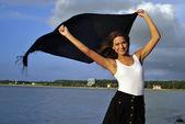 Dívka s černým šátkem je u moře na skalách — Stock fotografie