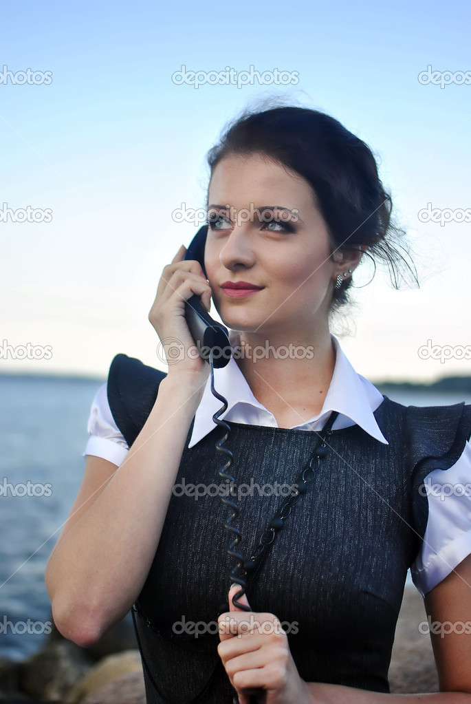 Girl with a telephone receiver in hand, space for text  Stock Photo #6932933