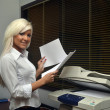 Pretty girl scans documents at the office — Stock Photo
