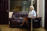 Girl sitting in the office on a leather couch — Stock Photo