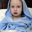 Little girl in blue robe resting on bed after shower with cup of — Stock Photo #7394942