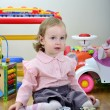 Little girl in a room with toys, playing with cars — Stock Photo