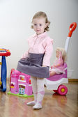 Little girl standing in a room with toys — Stock Photo
