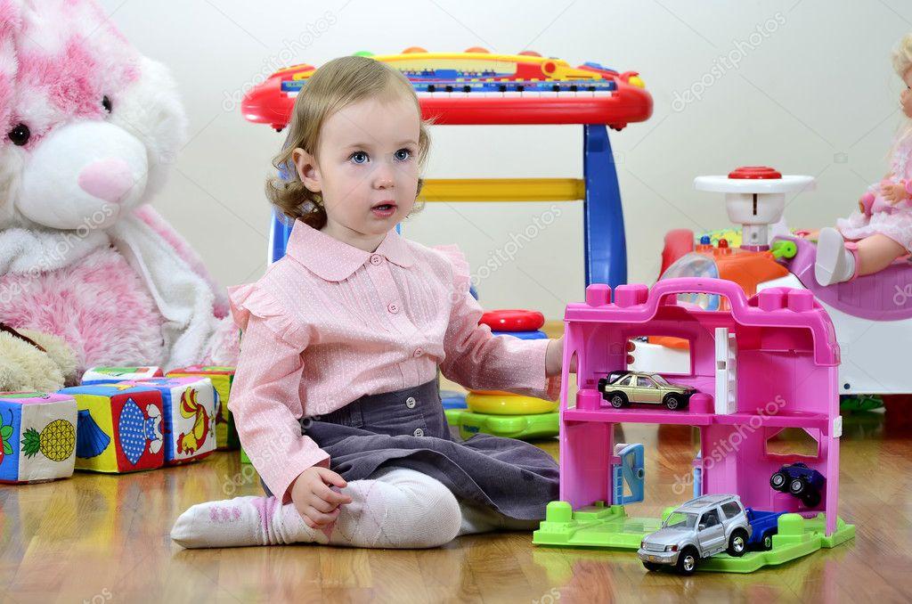 Kleines mädchen in einem raum mit spielzeug spielen