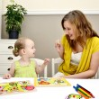 Little girl and mom playing in a children puzzle - Stock Photo