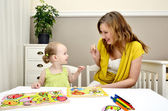 Little girl and mom playing in a children puzzle — Stock Photo