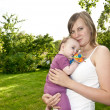 Young mother in the garden with a baby — Stock Photo