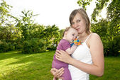 Young mother in the garden with a baby — Fotografia Stock