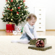 Little girl unpacks the gift at Christmas — Stock Photo