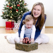 Little girl and her mother unpacks the gift at Christmas — Stock Photo