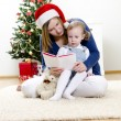 Girl and her mom reading book at Christmas — Stock Photo #7702197