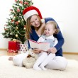 Girl and her mom reading book at Christmas — Stock Photo