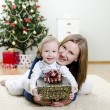 Little girl and her mother holding gift at Christmas — Stock Photo