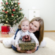 Little girl and her mother holding gift at Christmas — Stock Photo #7702223