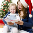 Girl and her mom reading book at Christmas — Stock Photo #7702248