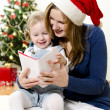 Stock Photo: Girl and her mom reading book at Christmas
