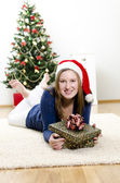 Christmas, the girl lying on the carpet with a gift — Stock Photo