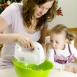 Stock Photo: Little girl and mother are preparing Christmas cookies