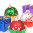 Christmas ornaments in cupcake liners with gifts - Stock Photo