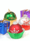 Christmas ornaments in cupcake liners with gifts — Stock Photo