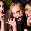 Three witches eat thin black snake — Stock Photo
