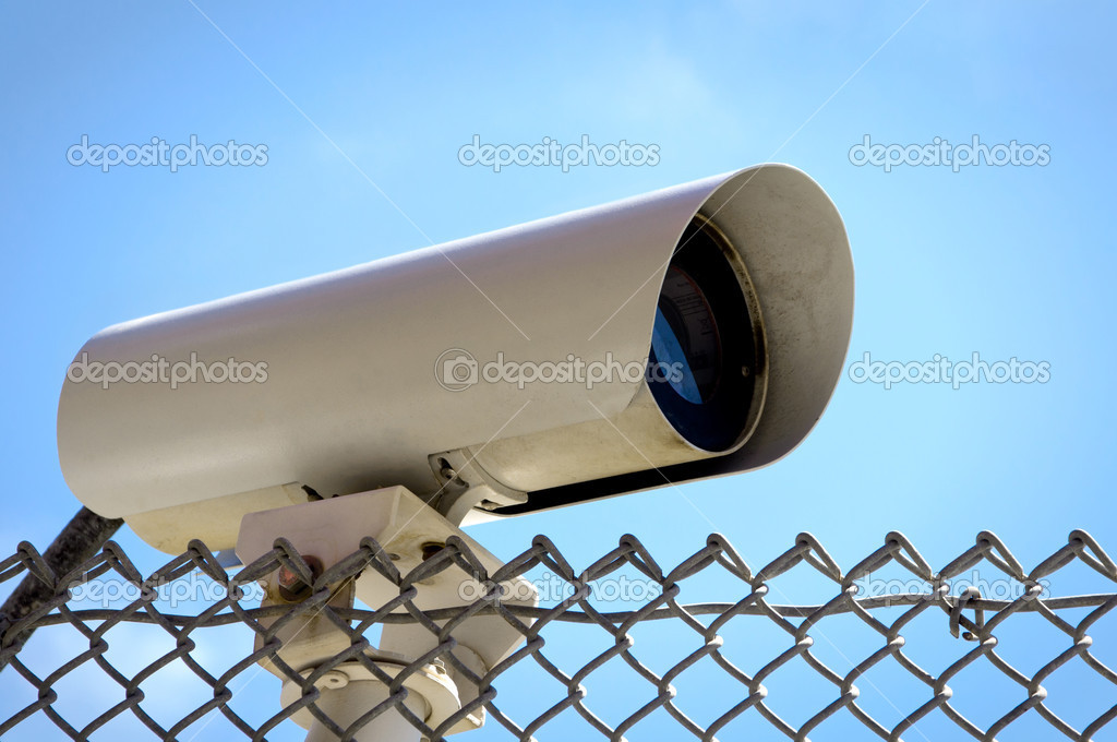 Security Camera on a Chain link Fence at the Open Sky  Stock Photo #6859195