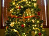 Ornamente, lichter und bänder auf hellen, grünen weihnachtsbaum — Stockfoto