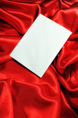 Blank card on red silk — Stock Photo