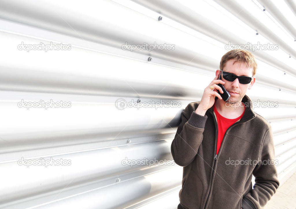 Young man talking on mobile phone against industrial background  — Stock Photo #6829302