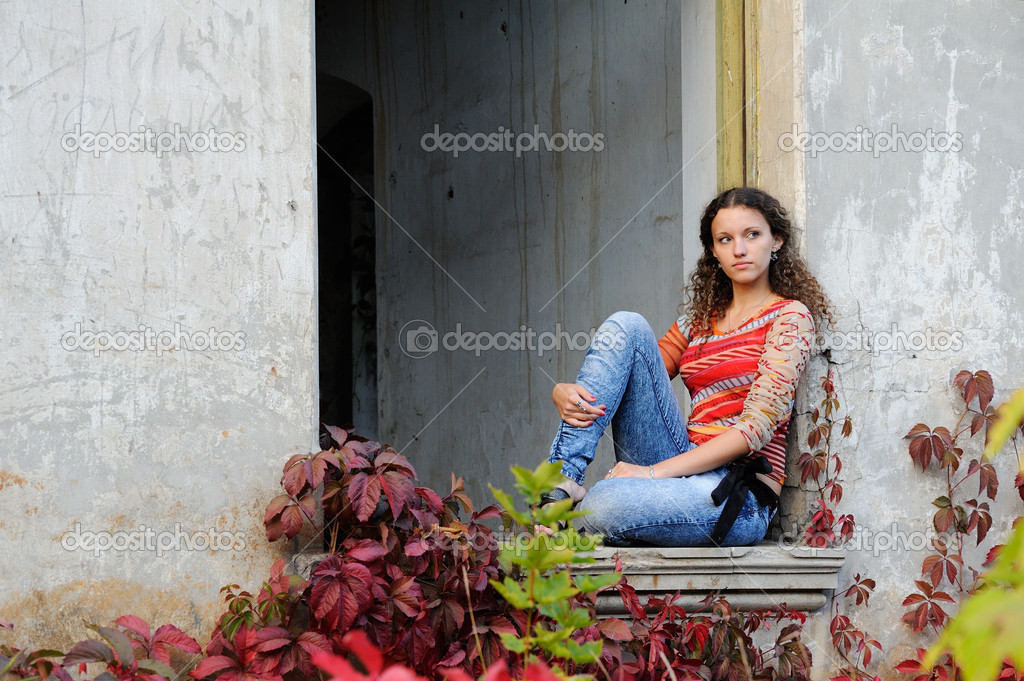 Girl sits in the window opening of the old ruined building — Stock Photo #6952283