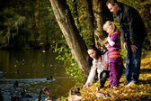 Young family in the autumn park — Stok fotoğraf