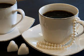Two cups of coffee, sugar and pearls — Stock Photo