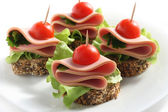 Canape with boiled sausage — Stock Photo