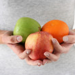 Apples and orange in hands of woman — Stock Photo