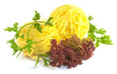 Raw pasta nests and green parsley and lettuce on white — Stock Photo