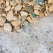 Pebbles and foam on the beach, close — Stock Photo
