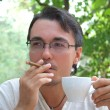 Young man smoking cigar and drinking coffee — Stock Photo
