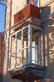 Old house with new plastic window in balcony — Stock Photo