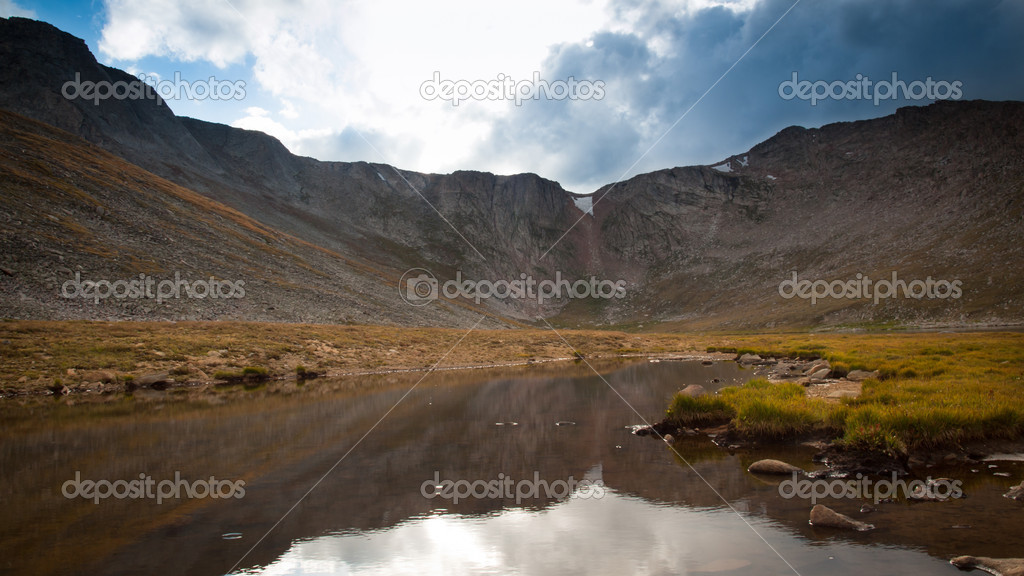 Beautiful Summit Lake reflects towering Mt. Evans and is surrounded by lush vegetation. Colorado.  Stock Photo #6887878