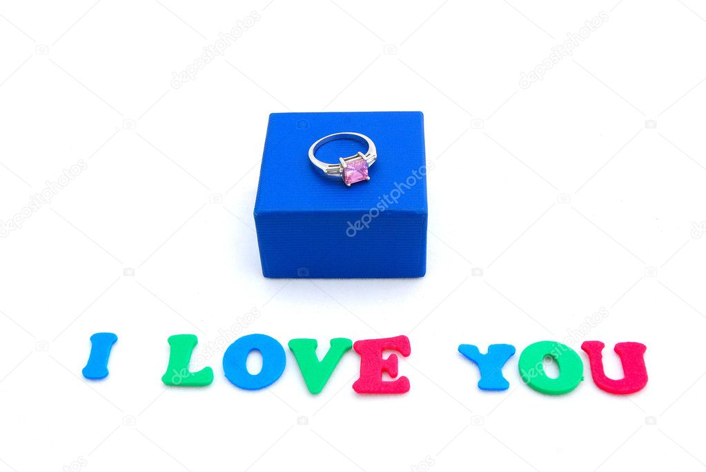 The words I LOVE YOU written with colorful foam letters with a blue gift box and diamond ring on top. Image isolated on white studio background. — Stock Photo #6860020