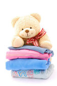 Teddy on stack of kids clothes — Stock Photo