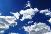 Ciel bleu avec des nuages blancs moelleux dans la lumière du jour — Photo