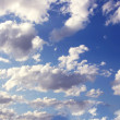 Blue sky with fluffy white clouds in day light — Стоковая фотография