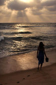 Girl on a beach on sunset — Stock Photo