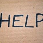 Help written on cardboard — Stock Photo #6904492