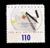 Stamp shows the envelope of a letter, pens and post it — Stockfoto