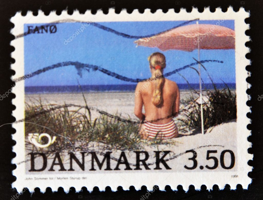 DENMARK - CIRCA 1991: A stamp printed in Denmark shows a woman back on the beach under the umbrella, circa 1991   Stock Photo #6904660