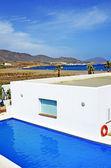 Niebieski basen w pobliżu domu na tle niebo z chmur i morze w spai — Zdjęcie stockowe