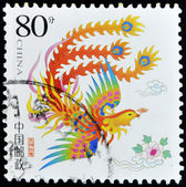 A stamp printed in China shows a colored bird with a flower in its beak — Stock Photo