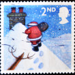 UNITED KINGDOM - CIRCA 2004: A stamp printed in England, shows Santa Claus, walking toward chimney in snow, circa 2004 - Stockfoto